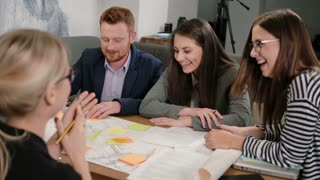 Woman offers good idea everyone is happy, high-fiving each other Creative business team meeting in startup office