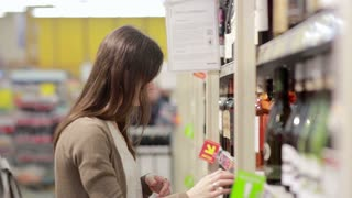 Woman selects the wine on the shelves in the store