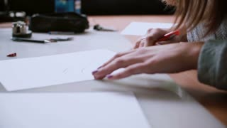 Woman sitting at the table, holding pencil and drawing layout on paper. Erase in sketch. Slider left, side view. 4K