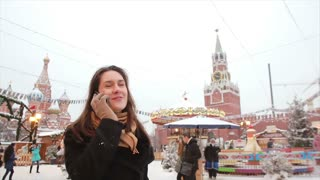 Woman talking on phone standing in the winter on the Red Square in Moscow, in front of Kremlin and St. Basil's Cathedral