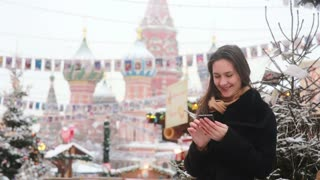 Woman talking on the phone standing in the winter on the Red Square in Moscow, in front of St. Basil Cathedral