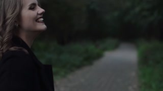 Woman turns her face, smiles to camera as she runs in nature holding the hand of a man. Blond hair is swaying.