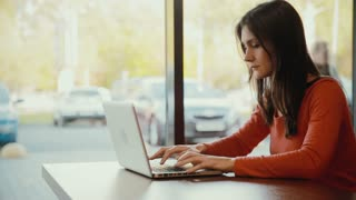 woman typing on laptop and smiling at cafe