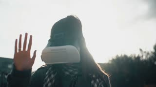 woman uses a virtual reality glasses in rear light at sunset 4k