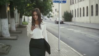 Woman uses smartphone walking in old city. slow mo