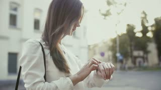 Woman uses smartwatch standing in old city slow mo