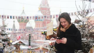Woman using a smartphone standing in the winter on the Red Square in Moscow, in front of St. Basil Cathedral
