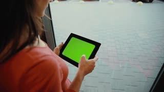 Woman using a tablet at the window. green screen