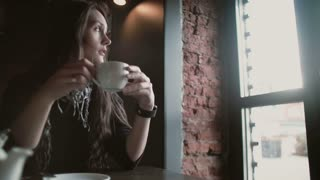 Woman using her smartwatch touchscreen device drinking coffee looking out the window in loft cafe 4k