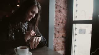 Woman using her smartwatch touchscreen device in loft cafe 4k