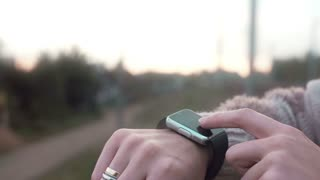 Woman using her smartwatch touchscreen device on a countryside background 4k