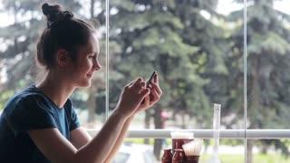 Woman using smartphone sitting near the window