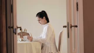 Woman using tablet and drinking coffee by table
