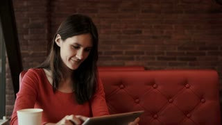 woman using tablet drinking coffee and smiling