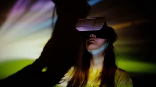 Woman using VR-helmet in the spotlight