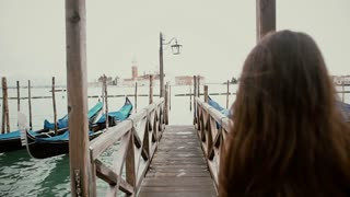 Woman walking on dock at Grand Canal Venice, Italy
