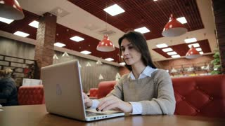 Woman working on modern laptop in cafe