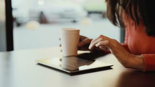 Woman working on tablet at cafe and drink coffee
