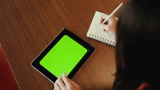 Woman  working on tablet, takes notes. greenscreen