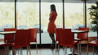 Women talks on the phone near the window in cafe.