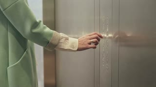 Women's hand presses button. elevator doors closed