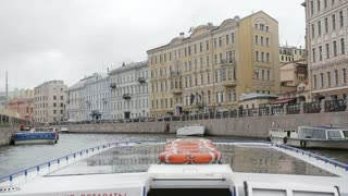 Wonderful view of city architecture from a river bus, turning left. Buildings on a river quay. St Petersburg, slow mo