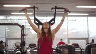 Working out in a sport club. Young sporty woman is doing pull-ups on sport equipment.