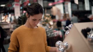 Young attractive brunette girl at the store chooses bright toys Christmas decor.
