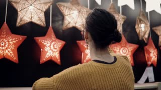 Young attractive brunette girl at the store chooses lamps Star Lights, Christmas decor.