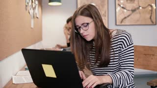 Young attractive girl working with laptop in a modern startup office