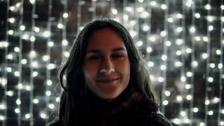 young attractive woman enjoying falling snow at Christmas night in front of the decorative wall full of sparkling lights