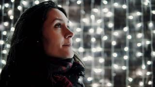 young attractive woman having fun catches the tongue falling snow at Christmas night, lights at background