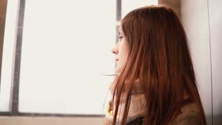 Young attractive woman in glass elevator going down. Brunette girl looking to the window and thinking. 4K