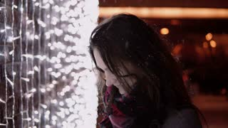 young attractive woman in the falling snow at Christmas night looking at the camera lights at background