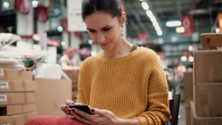 young attractive woman in the orange jacket uses a smartphone, sitting among the things in a store