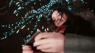 young attractive woman using smartphone at snowy Christmas night standing under a tree decorated with sparkling lights