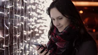 young attractive woman using smartphone in the falling snow at Christmas night standing near lights wall,