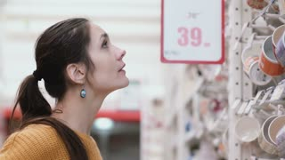 Young beatifull woman standing in front of cups in the supermarket shop and try to choose something. 4K