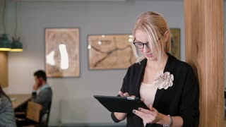 young beautiful blonde businesswoman uses a touchscreen tablet in the modern startup office. Slow mo, steadicam shot