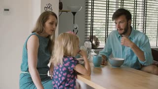 Young beautiful couple is having breakfast with their daughter in the morning. Slow motion