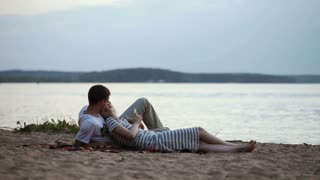 Young beautiful couple lying on the shore of the lake at sunset