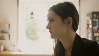 Young beautiful dark-haired woman having a cup of tea in the kitchen. Slow motion