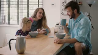 Young beautiful happy family of three is having breakfast at the kitchen table and laughing. Slow motion, Steadicam shot