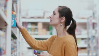 Young beautiful woman chooses baby food in the supermarket near the food shelf. 4K
