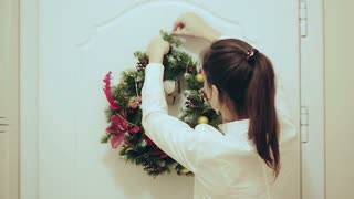 Young beautiful woman decorator hangs on the door a beautiful Christmas wreath