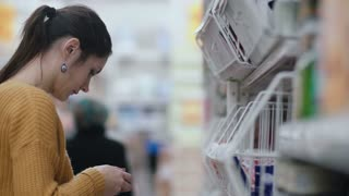 Young beautiful woman in supermarket standing in front shelfs and looking to something, then turns and walking away. 4K