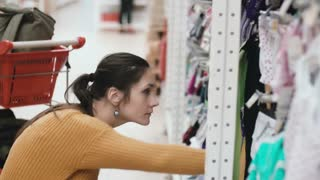 Young beautiful woman squatting in the supermarket and choosing baby clothes at the showcase. Female at the shop. 4K