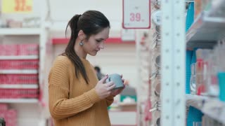Young beautiful woman standing in front of shelves with cups, holding one and try to choose something in supermarket. 4K