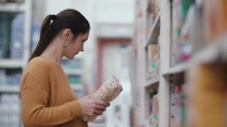 Young beautiful woman standing in front of shelves with groats, holding one and try choose something in supermarket. 4K