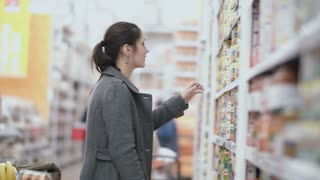 Young beautiful woman standing in front of shelves with grocery , holding one can and try choose in supermarket. 4K